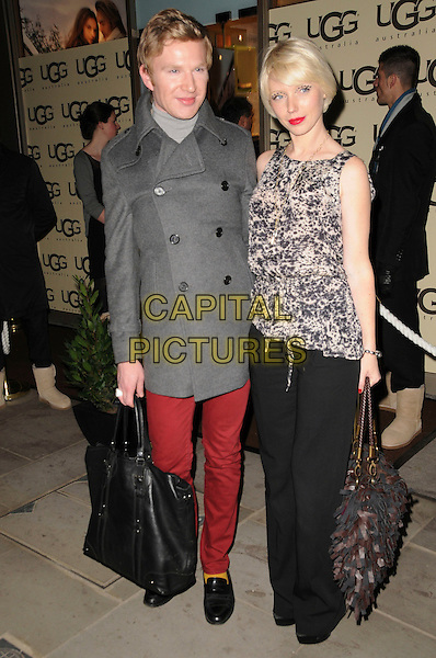 HENRY CONWAY & CHARLOTTE DUTTON.The UGG Australia: London Store Launch in Covent Garden, London, England..November 26th, 2008.full length red jeans denim trousers grey gray coat jacket black white sleeveless pattern top bag purse .CAP/CAS.©Bob Cass/Capital Pictures.