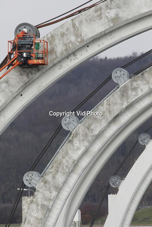 Foto: VidiPhoto<br /> <br /> DRIEL – Personeel van kabel- en hijsexpert Mennens Nederland hangt woensdag in en aan de kabels van het stuwcomplex bij Driel. In opdracht van Rijkswaterstaat worden daar deze week de verouderde kabels en kabelwielen vervangen. Dat gebeurt op het moment dat er geen hoogwater in de Rijn wordt verwacht. Omdat hoogwater maximaal vier dagen vooraf kan worden voorspeld, mogen de werkzaamheden ook niet langer duren. Door deze klus nu af te ronden, wordt straks tijd bespaard bij het grote werk deze zomer. Dan moet de zuidelijke vizierschuif (stuwboog) in delen worden verwijderd. Die werkzaamheden duren zo'n 16 weken. Vorig jaar werd de noordelijk boog vernieuwd. Dat werk was eerder ingepland, maar moest uitgesteld worden omdat bij voorbereidingswerkzaamheden een duiker om het leven kwam. De waterkeringen van Amerongen, Hagestein en Driel in de Rijn, hebben de enige stuwbogen ter wereld. De vizierschuiven van Amerongen en Hagestein zijn inmiddels vervangen. In 2020 moet het enigszins vertraagde project (met een aanneemsom van 100 miljoen euro) gereed zijn, inclusief de schilderwerkzaamheden. Hoofdaannemer is Siemens.