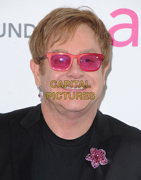 Elton John.The 21st Annual Elton John AIDS Foundation Academy Awards Viewing Party held at The City of West Hollywood Park in West Hollywood, California, USA..February 24th, 2013.oscars headshot portrait pink sunglasses shades brooch flower black .CAP/DVS.©DVS/Capital Pictures.