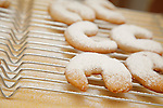 crescent cookies cooling on a baking rack sprinkled with powdered sugar