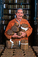 Cuba, March 1992: A worker holds finished cigars tied in bundles in front of the safe inside the Partagas factory in Havana. The finished cigars are kept in the safe for atleast a week in cupboards  with 18 degrees temp and at 80% humidity.