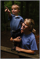 A young boy points and expresses concern on his face while watching a wildlife show with his mother. Model released image, can be used for multiple purposes.