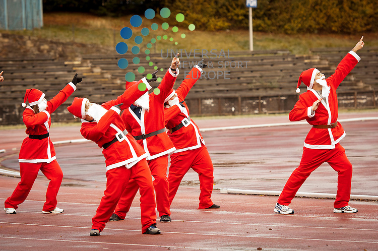 In a nod to Team GB's success in this year's Olympic Games, Santas from Team North Pole warm up at Meadowbank Stadium in preparation for the Great Edinburgh Santa Run.  The Santas want to encourage people to come out on Sunday morning (9 December) to don their Santa suits and run, walk or toddle around West Princes Street Gardens in aid of the When You Wish Upon a Star foundation..Picture: Pavol Mraz/Universal News And Sport (Scotland). 5/ December 2012.