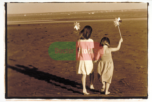 young girls walk on beach with pinwheels