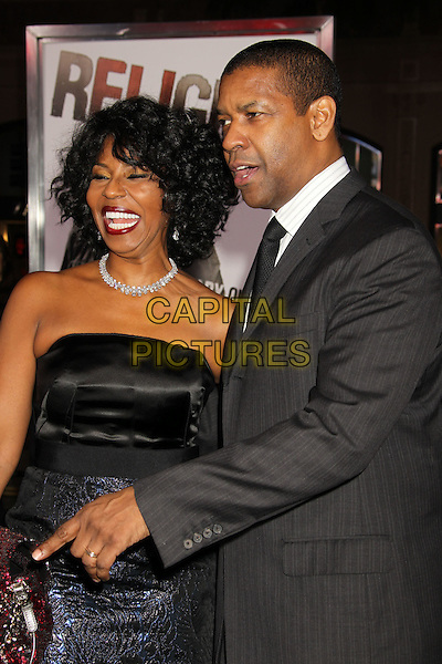 "PAULETTA & DENZEL WASHINGTON.""The Book Of Eli"" Los Angeles Premiere held at Grauman's Chinese Theatre, Hollywood, California, USA..January 11th, 2009.half length black blue shiny dress grey gray suit jacket married husband wife pattern patterned necklace diamond earrings strapless smiling profile hand pointing finger .CAP/ADM/MJ.©Michael Jade/AdMedia/Capital Pictures."