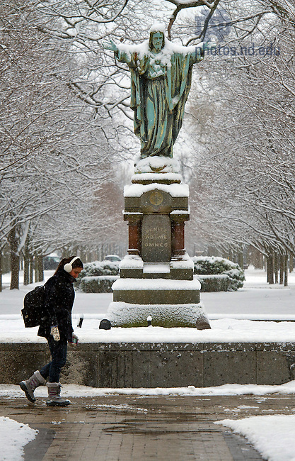 December 9, 2011; A student walks in front of the Jesus statue on main quad. Photo by Barbara Johnston/University of Notre Dame.