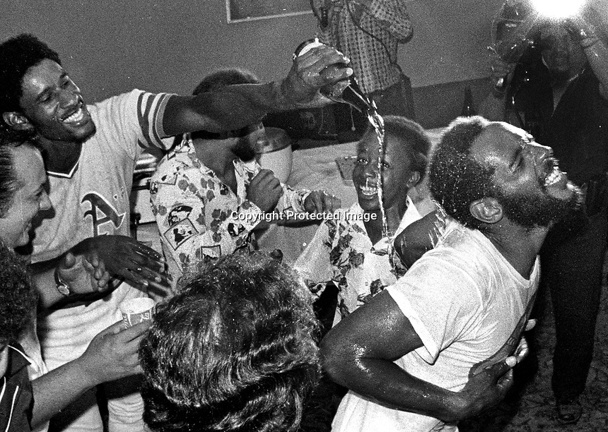 Oakland A's celebrate AL Division win in  1975, Claudell Washington dumps champane on the back of Billy North..youngster in the center is A's clubhouse boy, Stanley Burrell (Ak M.C. Hammer)<br />(photo/Ron Riesterer)