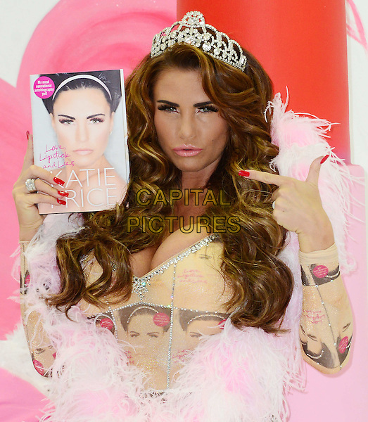 Katie Price (aka Jordan)<br /> At a photocall to launch her autobiography - 'Love, Lipstick And Lies' at The Worx, London, England.<br /> October 22nd, 2013<br /> half length leotard catsuit cover print crown tiara  beige silver pink fur book hand on hip cleavage finger pointing    <br /> CAP/BF<br /> &copy;Bob Fidgeon/Capital Pictures