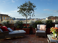 The terrace, with a view of St. Peter's Basilica, holds a wicker chaise longue and chair by Manutti, pots of thyme and rosemary, and a pomegranate tree.