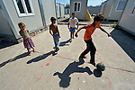 "THIS PHOTO IS AVAILABLE AS A PRINT OR FOR PERSONAL USE. CLICK ON ""ADD TO CART"" TO SEE PRICING OPTIONS.   Roma children play football amid shipping containers that have been converted into houses in Makis, a village outside of Belgrade, Serbia. These Roma families were evicted from an urban squatter settlement in 2012 to make way for construction of new apartments and office buildings. The shipping containers they now call home, which were provided at no cost by local authorities, are far from the city center."