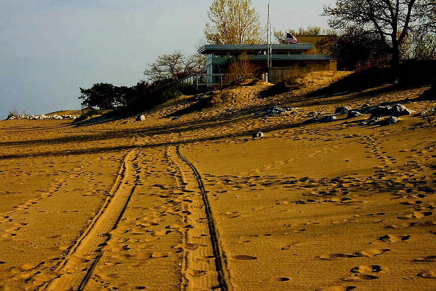 A pair of tire tracks running into the distance on a sandy beach.