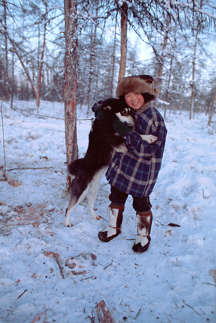 Misha Elrika, an Even boy, plays with a dog at a reindeer herders' camp in Northern Evensk. Magadan Region, Russia