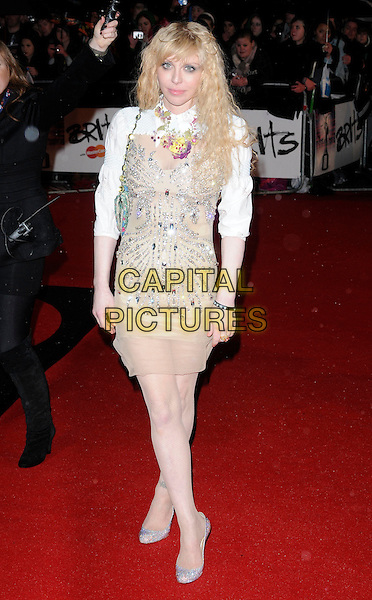 COURTNEY LOVE.Arrivals the Brit Awards 2010 held at Earls Court, London, England..February 16th 2010 .Brits full length white shirt beige strapless dress top bag pink flower necklace beaded crystals shoes christian louboutin jewelled glittery pale skin bare legs .CAP/CAN.©Can Nguyen/Capital Pictures.