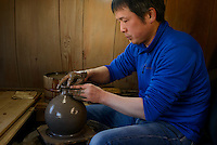 Potter Isezaki So in his workshop. Bizen city, Okayama Pref, Japan, January 29, 2014. The city of Bizen in central Japan is famous for Bizen-ware pottery. It is also one of Japan's main traditional sword making regions, home to Osafune sword-makers and polishers.