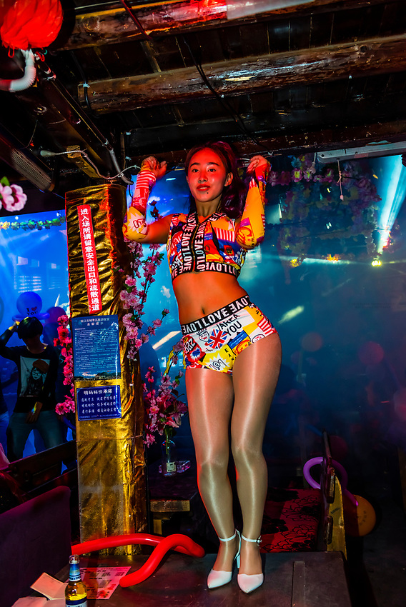 Go go girls in clubs along Bar Street (Xinhua Street) in Dayan (The Old Town), Lijiang, Yunnan Province, China.