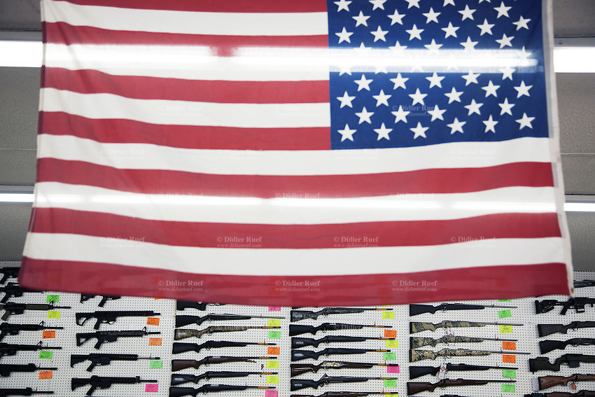 "USA. Arizona state. Tucson. Second Amendment Sports is a gun shop selling firearms with over 1'000 guns in stock. An american flag and semi-automatic rifles on display for sale. A firearm is a portable gun, being a barreled weapon that launches one or more projectiles often driven by the action of an explosive force. Most modern firearms have rifled barrels to impart spin to the projectile for improved flight stability. The word firearms usually is used in a sense restricted to small arms (weapons that can be carried by a single person). The right to keep and bear arms is a fundamental right protected in the United States by the Second Amendment of the Bill of Rights in the Constitution of the United States of America and in the state constitutions of Arizona and 43 other states. The flag of the United States of America, often referred to as the American flag, is the national flag of the United States. It consists of thirteen equal horizontal stripes of red (top and bottom) alternating with white, with a blue rectangle in the canton (referred to specifically as the ""union"") bearing fifty small, white, five-pointed stars arranged in nine offset horizontal rows of six stars (top and bottom) alternating with rows of five stars. 30.01.16 © 2016 Didier Ruef"