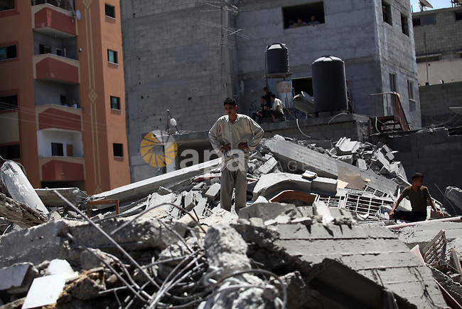 Palestinians look at the remains of al-Qassam mosque, which witnesses said was hit by an Israeli air strike, in Nuseirat refugee camp in the central Gaza Strip on August 9, 2014. Israel launched more than 20 aerial attacks in Gaza early on Saturday and militants fired several rockets at Israel in a second day of violence since a failure to extend an Egyptian-mediated truce that halted a month long war earlier this week. The Israeli military said that since midnight it had attacked more than 20 sites in the coastal enclave where Hamas Islamists are dominant, without specifying the targets. Medical officials in Gaza said two Palestinians were killed when their motorcycle was bombed and the bodies of three others were found beneath the rubble of one of three bombed mosques. The air strikes which lasted through the night also bombed three houses, and fighter planes also strafed open areas, medical officials said. Photo by Ashraf Amra