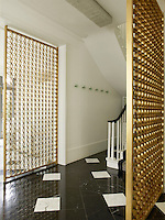 In the entrance hallway are two gold 1960s screens. The hall is spacious with a luxurious black and white marble floor with under-floor heating.