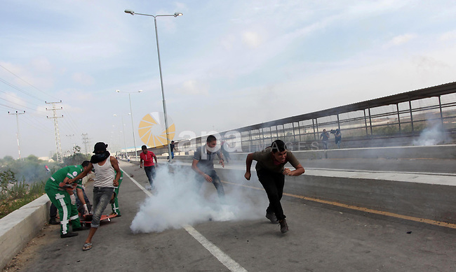 Palestinian protesters react from a tear gas canister fired by Israeli security forces during clashes next to the border fence with Israel, at the Erez crossing in the northern Gaza strip, on October 13, 2015. A wave of stabbings that hit Israel, Jerusalem and the West Bank this month along with violent protests in annexed east Jerusalem and the occupied West Bank, has led to warnings that a full-scale Palestinian uprising, or third intifada, could erupt. The unrest has also spread to the Gaza Strip, with clashes along the border in recent days leaving nine Palestinians dead from Israeli fire. Photo by Ashraf Amra