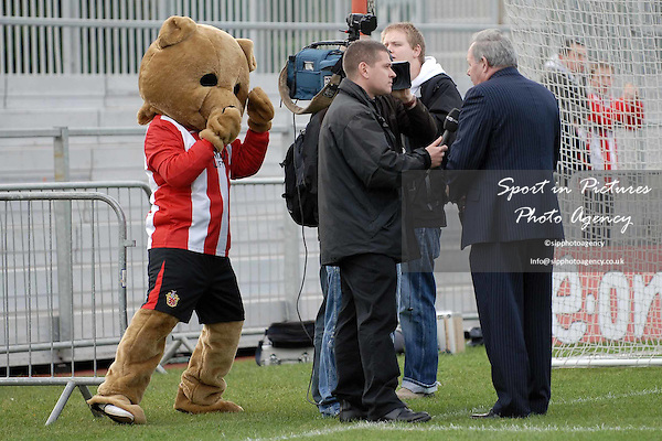 As Barry Fry (Peterborough Director of Football) is interviewed by one of the TV crews, Urchin the bear (AFC Hornchurch mascot) tries to put him off. AFC Hornchurch Vs Peterborough United. FA Cup 1st round. The Stadium. Upminster. 09/11/08 Credit Garry Bowden