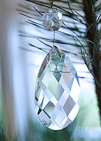 The Christmas tree is decorated with clear glass prisms shining in the winter light