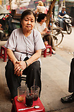VIETNAM, Hanoi, a portrait of Miss Thai, the owner of Cafe Nang sitting on a stool if front of her coffee shop, in business for over 50 years