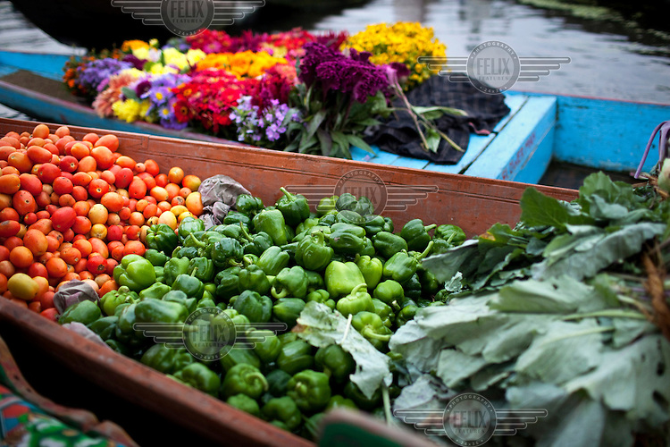 A floating market consisting of shikaras, or small wooden boats, on Lake Dal, selling vegetables and flowers.