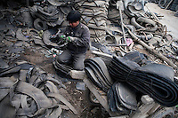Men work to recycle rubber tires in Linxia, Gansu Province, China.
