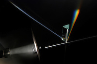 WHITE LIGHT IS REFRACTED BY A TRIANGULAR PRISM<br /> White light passes through prism and refracts<br /> The light source passes through a slit that focuses the light to precisely hit the prism, refracting into spectrum. The dispersion of light through the prism is projected onto the background.