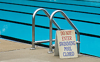 A sign marks the closing of one of the pools in the late afternoon at a Westerville, Ohio, public park.<br />