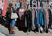 Vrouw zoekt kleding op de Noordermarkt in Amsterdam
