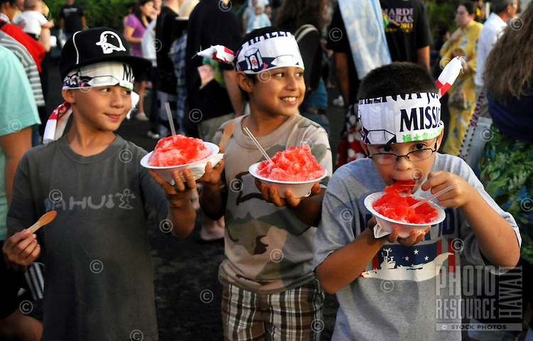 Three youngsters enjoying a shave ice treat at an obon (Japanese dance) festival.