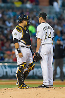 Charlotte Knights catcher Josh Phegley (4) has a chat with starting pitcher Dylan Axelrod (24) during the International League game against the Gwinnett Braves at BB&T Ballpark on April 16, 2014 in Charlotte, North Carolina.  The Braves defeated the Knights 7-2.  (Brian Westerholt/Four Seam Images)