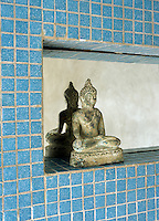 A Buddha sits on a mirrored niche in a bathroom decorated in turquoise mosaic tiles