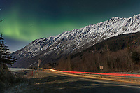 winter landscape shows Northern Lights (Aurora Borealis) in sky above moonlight on the Chugach Mountains along Turnagain Arm and  Seward Highway  car lights  January 2014