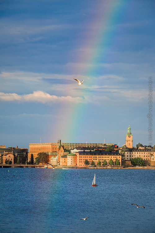 Regnbåge  över Stockholms slott och en segelbåt på Riddarfjärden