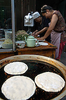 Two women preparing crepe dishes to sell at a street stall in the Muslim district of Daqingzhen Si in Xi'an, Shaanxi, China.