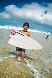 USA, Oahu, Hawaii, a young boy holds half of a broken surfboard at Pipeline Beach on the North Shore