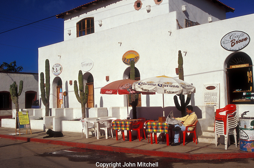 Man reading a newspaper at an outdoor cafe in the Spanish colonial town of Todos Santos , Baja California Sur, Mexico