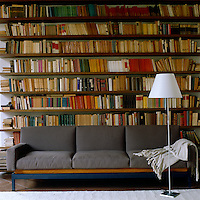 A grey, yellow and blue sofa stands infront of a wall of books in this library-cum-living room