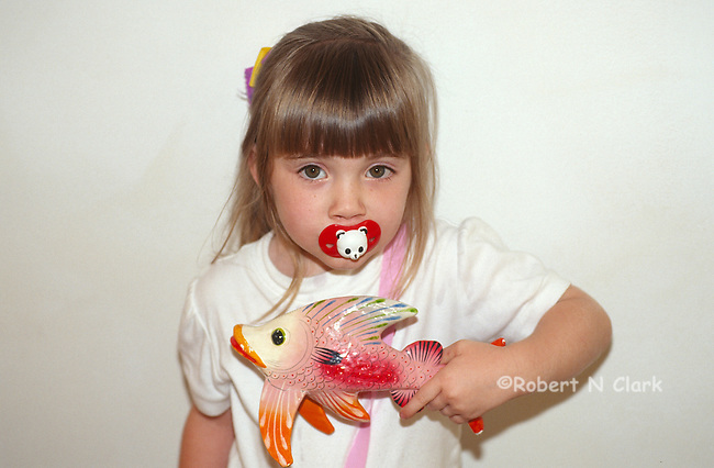 Girl with pacifier and fish sculpture
