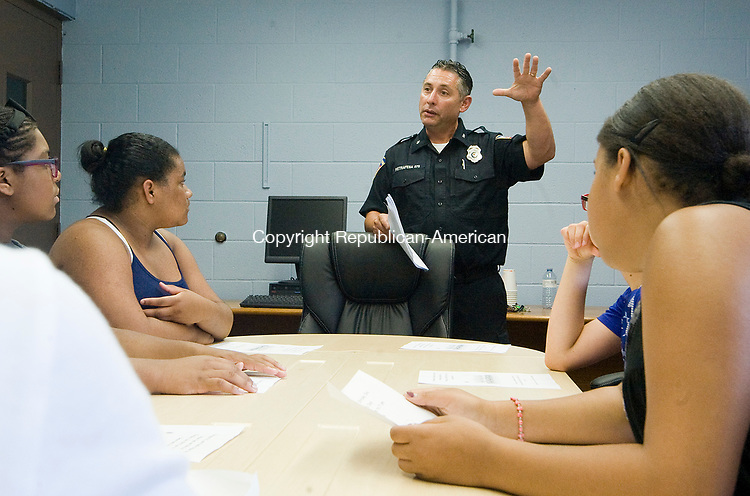 TORRINGTON, CT-071817JS04--Torrington police officer Anthony Pietrafesa talks with students who are participating in the Teen Outreach Program at the Connecticut junior Republic, Tuesday at the newly opened Torrington Police Department's community outreach office at Coe Memorial Park Civic Center. Officer Pietrafesa was organizing help for the PAL and Family Strides Inc. annual Kids Day which will be held Thursday at Best Park Pool. <br />  Jim Shannon Republican-American