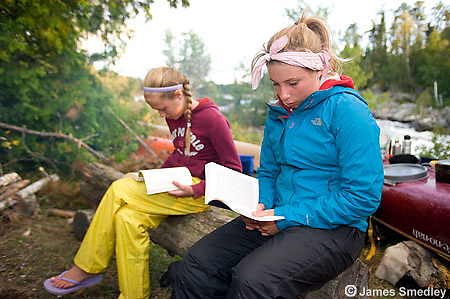Two young girls reading their books at the wilderness campsite.