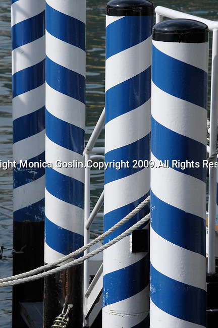 Blue and white poles of a dock in Menaggio on Lake Como, Italy.