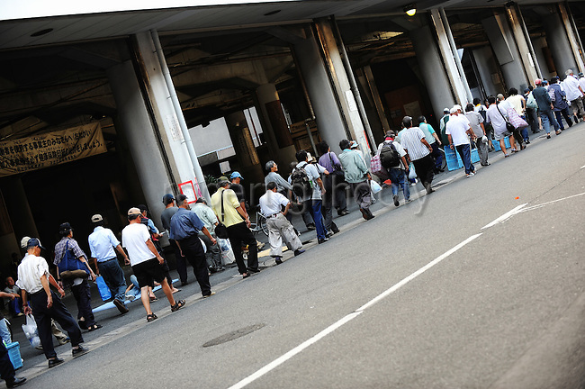 Unemployed people, many of them with no fixed abode, line up for beds at shelters outside the Nishinari Labor Welfare Center in the Kamagasaki district of Osaka, Japan on July 23 2008. Thousands of homeless people flock to the center daily in hope of securing day labor work, such as hands on building sites - jobs that pay around $US70 pounds per day..