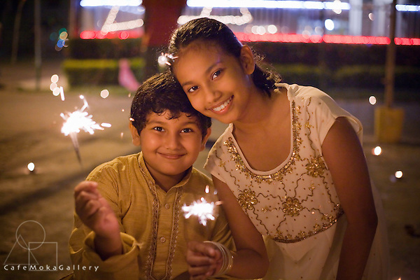 Divali,Hindu festival of light, brother and sisiter, Trini-Indian girl with  a starburst from a deya