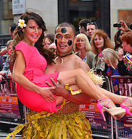 Lizzie Cundy<br /> The &quot;Bula Quo!&quot; UK film premiere, Odeon West End cinema, Leicester Square, London, England.<br /> July 1st, 2013<br /> half length pink flower in hair grass skirt lifting carrying holding  <br /> CAP/BF<br /> &copy;Bob Fidgeon/Capital Pictures