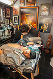 USA, Los Angeles, individuals getting a tattoo in a parlor off the Venice Boardwalk