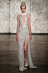 Model walks runway in a jeweled Chantilly lace side slit high neck sheath with removeable flower collar, from Inbal Dror Fall 2018 bridal collection on October 5, 2017; during New York Bridal Fashion Week.