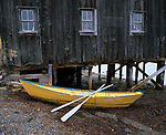 Lunenburg County, Nova Scotia<br /> Yellow dory and oars rest at the low tide line below th weathered Dory Shop on the Lunenburg waterfront